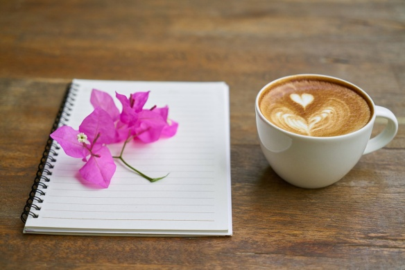 coffee and notebook with pink flower